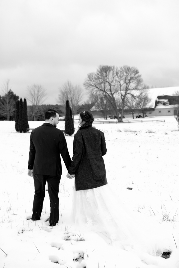 bride and groom walking winter wedding at Waterstone Estate and Farms