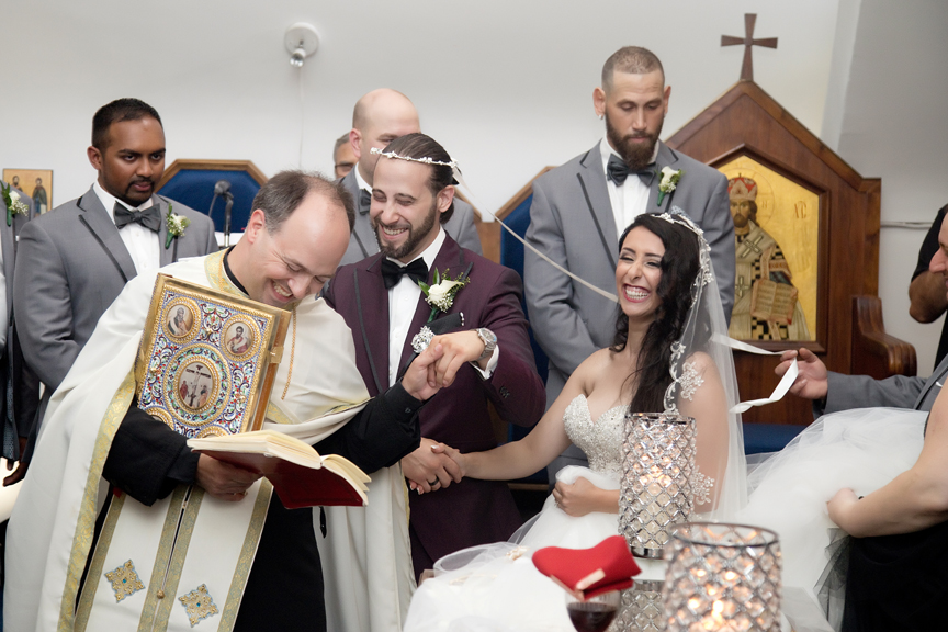 happy couple walking around alter wedding ceremony at All Saints Greek Orthodox Church